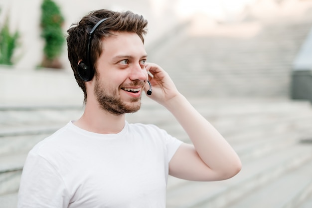 Man with headset in the city smiling