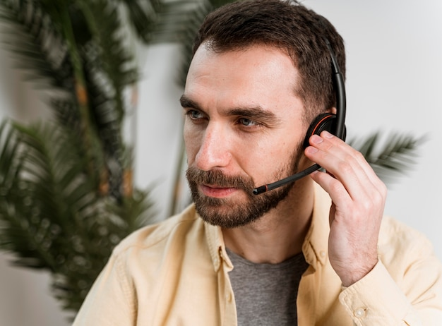 Uomo con auricolare che ha videochiamata sul computer portatile