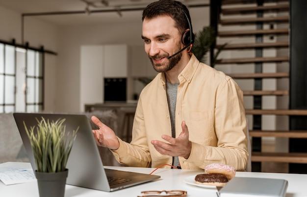 노트북에 영상 통화를 갖는 헤드셋을 가진 남자