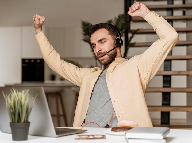 ノートパソコンでビデオ通話をしているヘッドセットを持つ男
