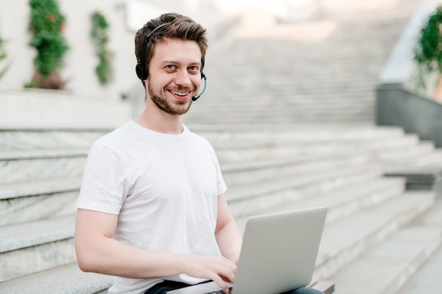 Man with headset and laptop outdoors