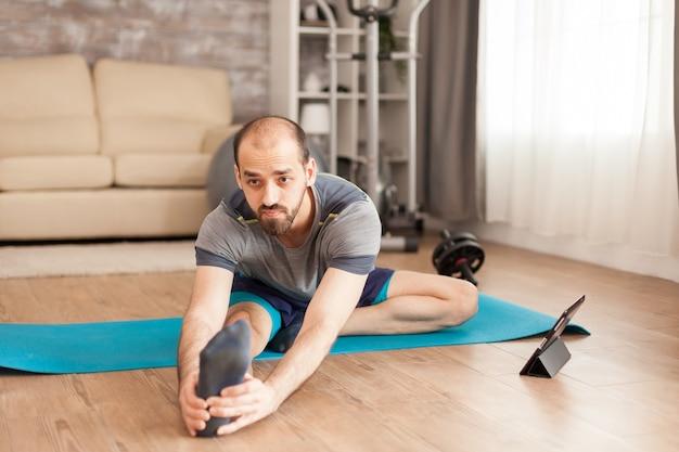 Мужчина со здоровым телом делает растяжку ног на коврике для йоги дома во время изоляции от коронавируса.