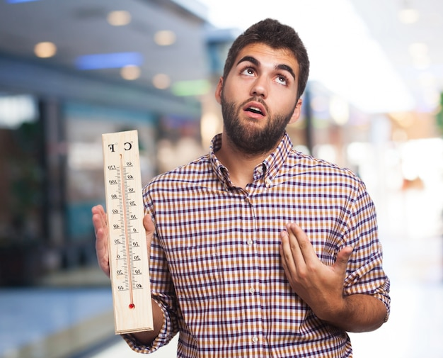 Man with heat holding a large thermometer