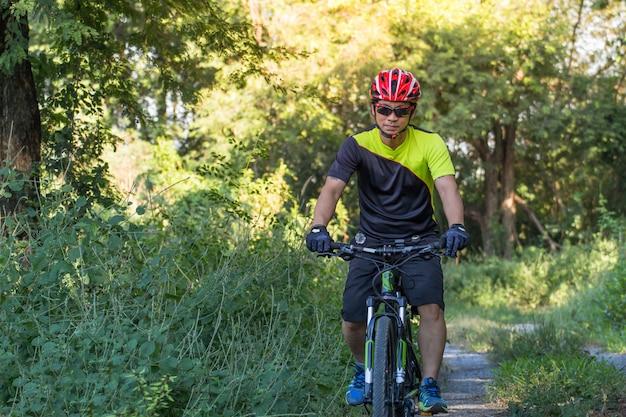 Человек с перчаткой шлема для безопасности ехать велосипед на сельской дороге вдоль леса, катании на лыжах