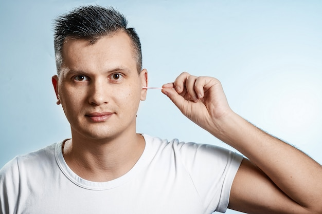 The man with the help of a hygienic cotton swab is reading his ear.
