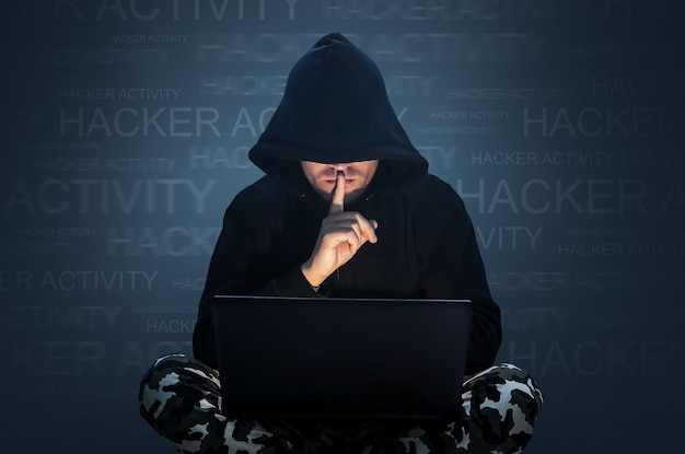 Man with hidden face working at a computer. holding a finger to his mouth. computer hacker stealing data from a laptop concept for network security, identity theft and computer crime