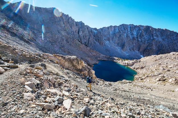 シエラネバダ山脈、カリフォルニア、米国を歩くハイキング用品を持つ男