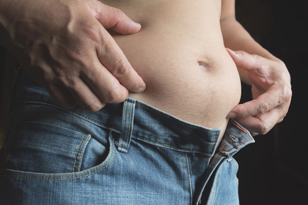 Man with his belly isolated on black background. overweight and weight loss concept.