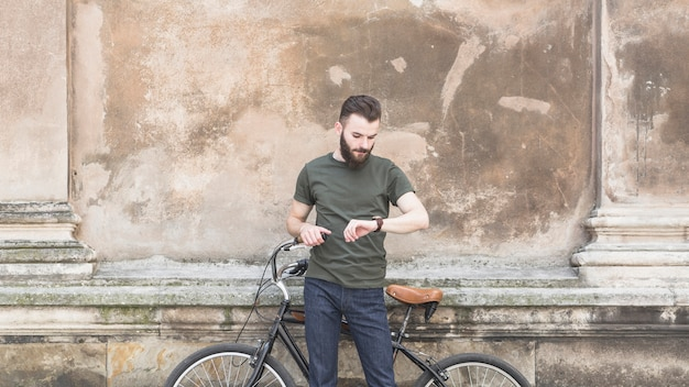 Man with his bicycle looking at time in wrist watch