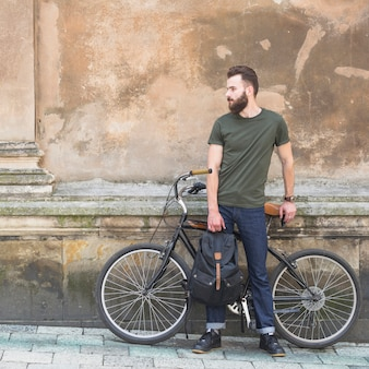 Man with his bicycle standing in front of old wall