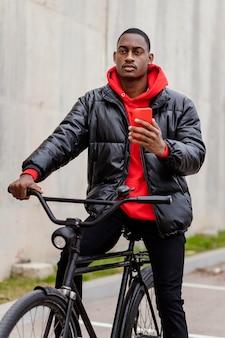 彼の携帯電話を使用して彼の自転車を持つ男