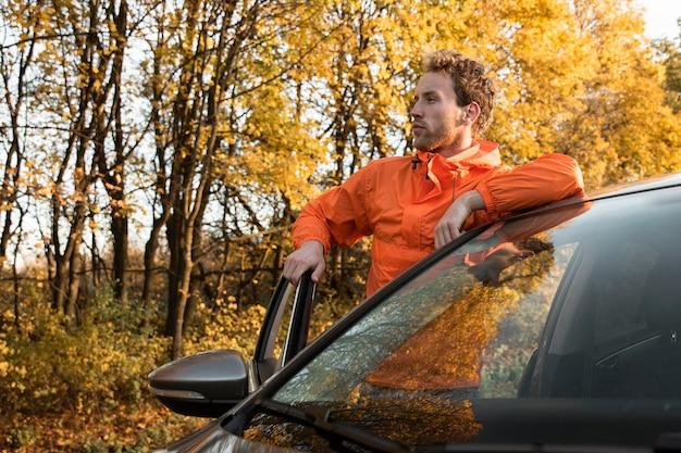 Человек со своей машиной на открытом воздухе в поездке