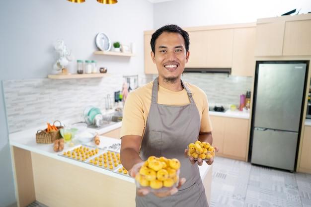 自宅でイードムバラクのためのnastarケーキを作るカメラに微笑んで彼の料理を持つ男