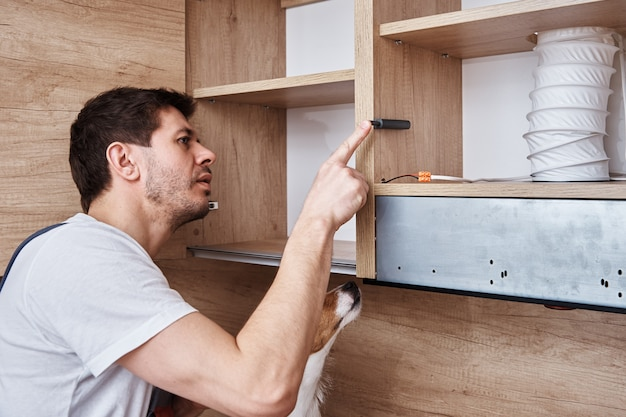 Man with his dog assembling kitchen cabinet