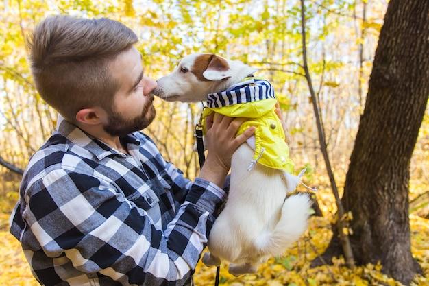 秋の公園で彼の犬と男。屋外でラッセルテリアと遊ぶ男。ペットと人