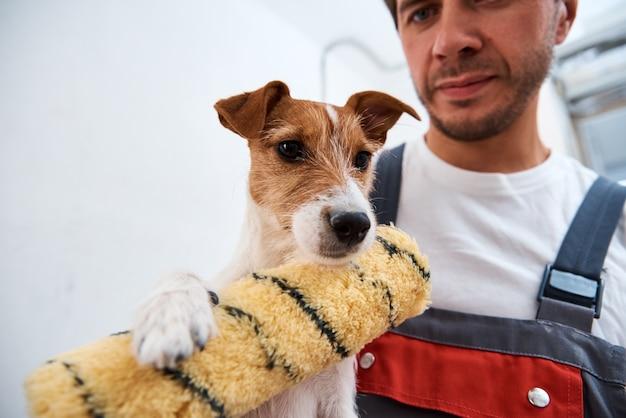 방에서 개조 작업을하는 그의 개를 가진 남자. 개와 주인의 좋은 관계