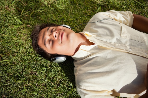 Man with his eyes closed while using headphones to listen to music as he lies down