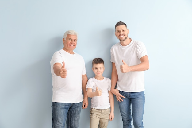 色の壁に親指を立てるジェスチャーを示す彼の父と息子を持つ男