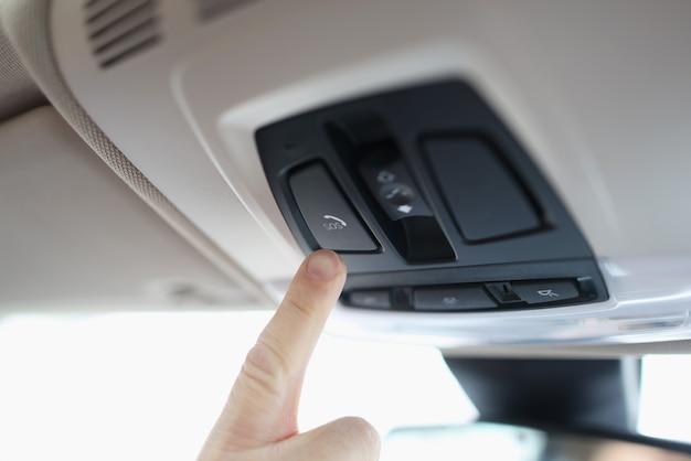 Человек с пальцем, нажав аварийную кнопку в автомобиле крупным планом