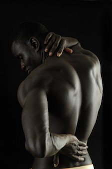 Man with his hand on the back because you have pain, black background