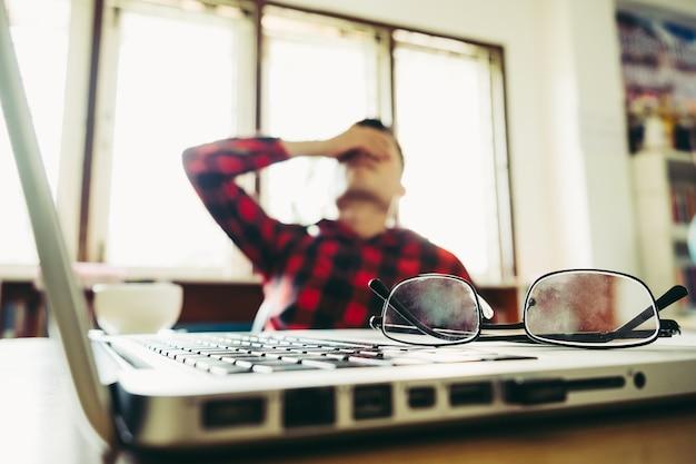 机の上に眼鏡をかけてラップトップコンピュータとノートブックで作業することからブレーキを奪う彼の顔を手にした彼の手の男。ストレス/休息/緊張/失敗/落胆/うつの概念