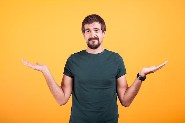 スタジオで黄色の背景にサインオンわからないことを示している彼の手を上げた男。不確かな男