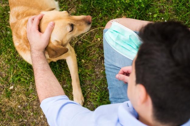 Covid-19 전염병 동안 공원에 앉아 그의 래브라도 개를 가진 남자