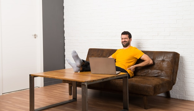 Man with his laptop in a room suffering from backache for having made an effort