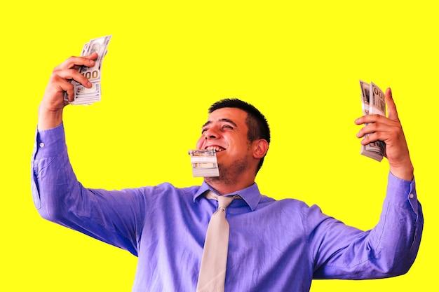 노란색 배경에 고립 된 그의 급여를 가진 남자입니다. 회사원과 달러입니다. 최고 관리자의 행복한 얼굴입니다. 스마트 셔츠와 넥타이에 남자입니다.