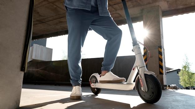 Uomo con il suo scooter in un parcheggio al chiuso indoor