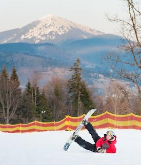 スキー斜面に彼のスノーボードを持つ男