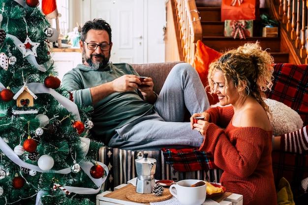 家でクリスマスのお祝いの間にコーヒーを飲み、話している彼の妻と一緒に男。クリスマスの前夜に朝食をとる白人カップル。飾られたクリスマスツリーとリビングルームのカップル。
