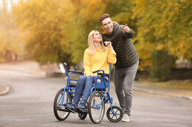 Man with his wife in wheelchair outdoors on autumn day