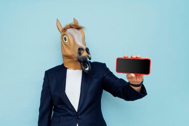 青い背景で隔離のポーズポーズで馬マスクを持つ男。人々のライフスタイルの概念。コピースペースをモックアップします。空の黒い画面で携帯電話を保持します
