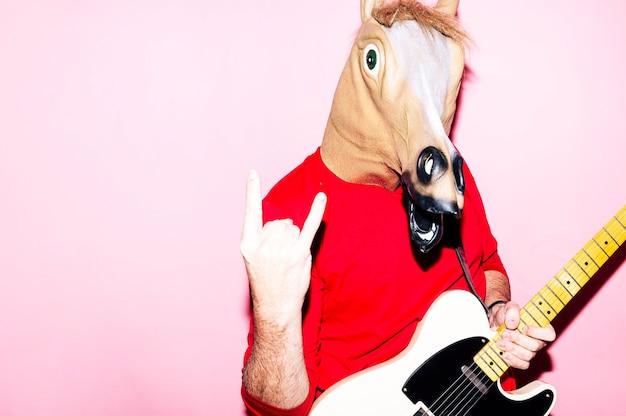 エレクトリックギターを弾く馬のマスクを持つ男