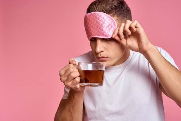A man with a hot drink and a cup of tea pink mask for a vigorous morning sleep