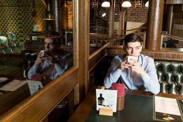 Uomo con bevanda calda rilassante nella caffetteria
