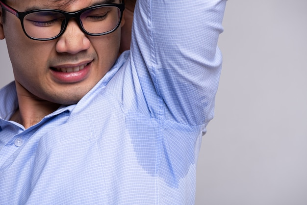 Человек с гипергидрозом потливость на одежде. концепция здравоохранения.