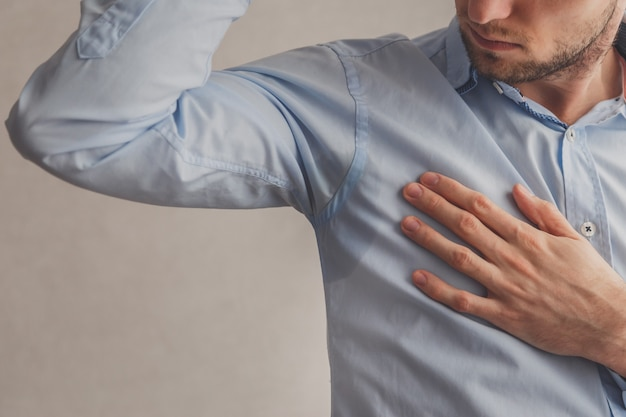 Man with hyperhidrosis sweating very badly under armpit in blue shirt, on grey.