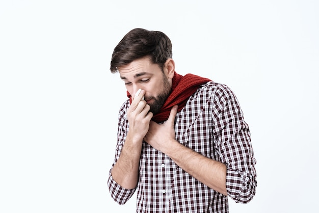 A man with a ill catches his nose on a white background