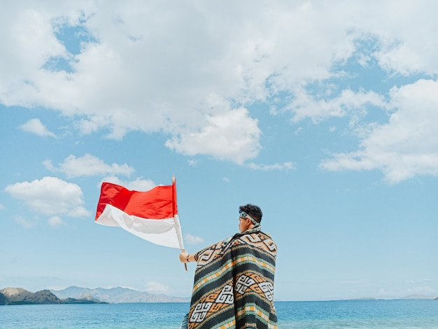 A man with indonesian traditional cloth called kain songket waving indonesia flag under blue sky