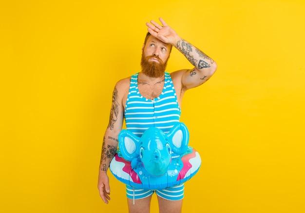 코끼리와 함께 풍선 도넛을 가진 남자가 수영할 준비가 되었습니다.