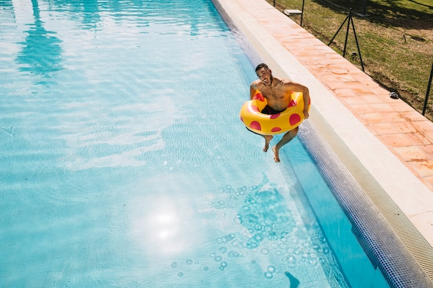 Man with inflatable ring jumping into pool