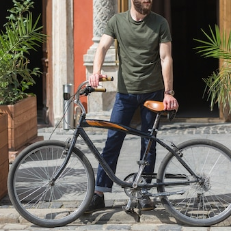Man with is bicycle standing on sidewalk
