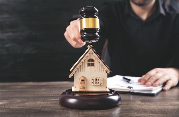 裁判官のガベルと家のモデルを持つ男。不動産弁護士