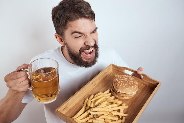 Человек с нездоровой пищей, нездоровой пищей, гамбургером и картофелем