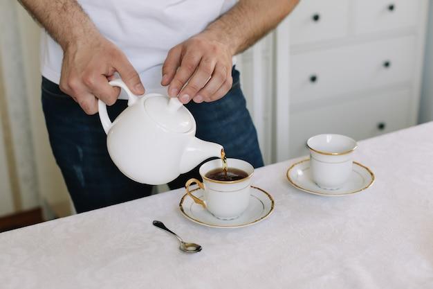 Человек с чайником, заваривающим чай