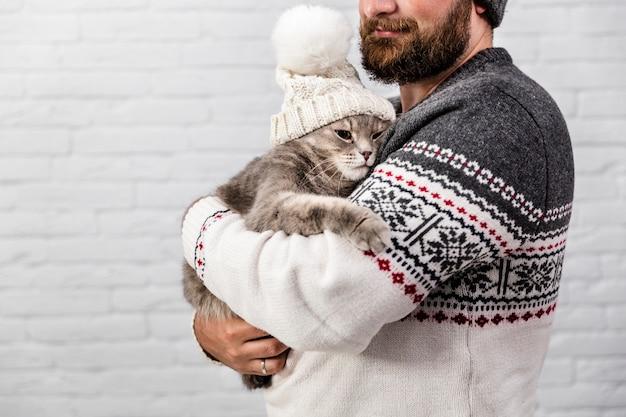冬の毛皮の帽子をかぶっている子猫を持つ男