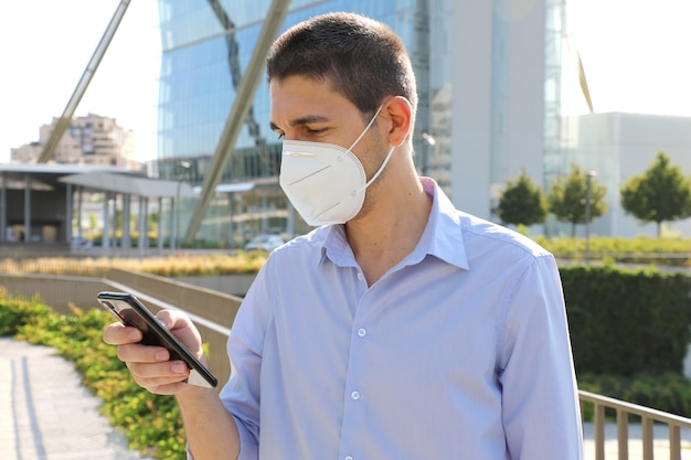 Man with kn95 protective mask calling with smartphone in modern city