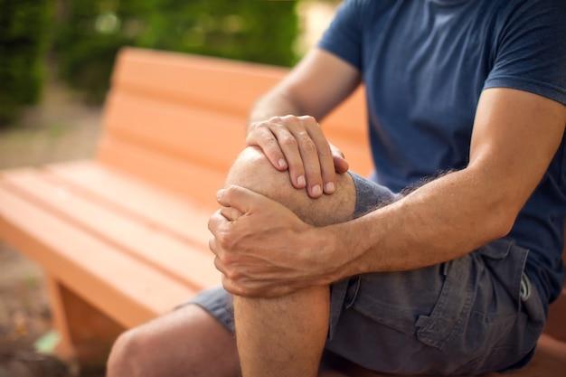 Человек с болью в колене сидит на скамейке в парке. концепция здравоохранения и медицины